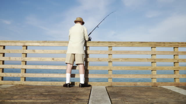 WS Senior man fishing off pier / Jacksonville Beach, Florida, USA