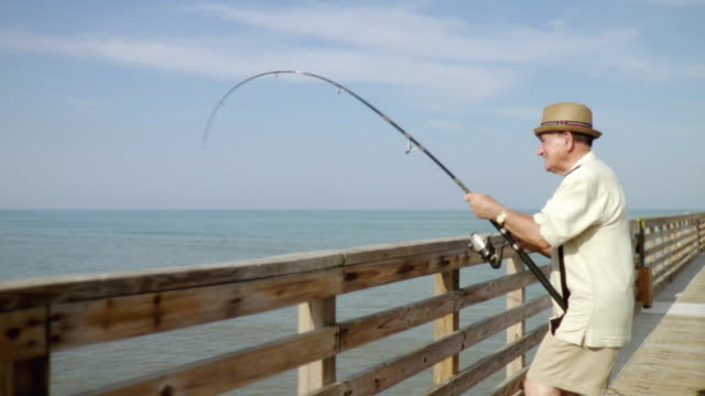 MS Senior man fishing on pier / Jacksonville Beach, Florida, USA