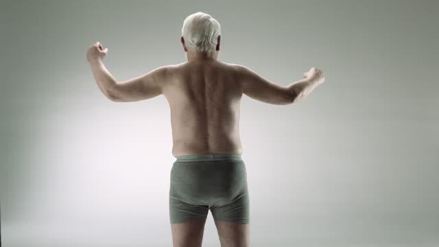 Senior man flexing muscles