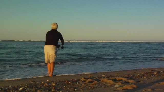 MS, Senior man fly fishing on beach, rear view, North Truro, Massachusetts, USA