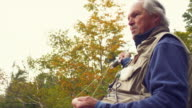 CU LA Senior man fly fishing, standing on lake shore, Manchester, Vermont, USA