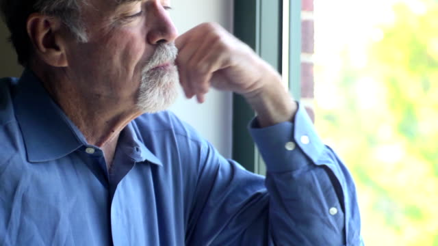 Senior Man blickt auf Fenster