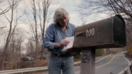 MS Senior man getting his mail out of mailbox / Kingston, New York, USA