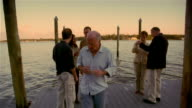 Senior man having heart attack during party on lakeside dock