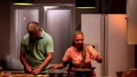 Senior man helping his wife in kitchen, Delhi, India