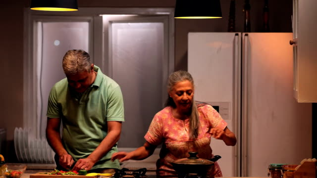 Senior man helping his wife in kitchen, Delhi, India