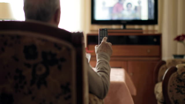Senior man holding a tv remote control