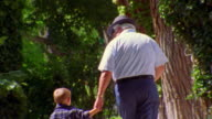 REAR VIEW senior man holding hands with boy, walking away from camera + putting hat on boy