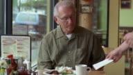 CU, Senior man in diner getting check