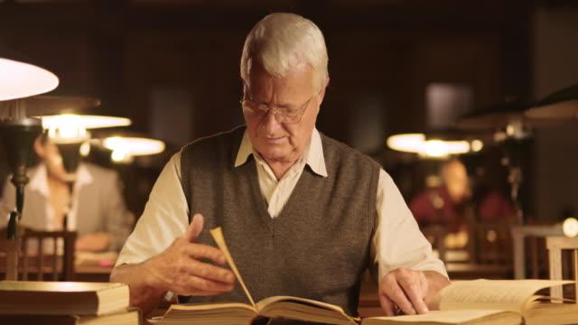 DS Senior man in bibliotheek zoeken naar informatie in boeken