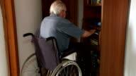 senior man in wheelchair approaches bookcase