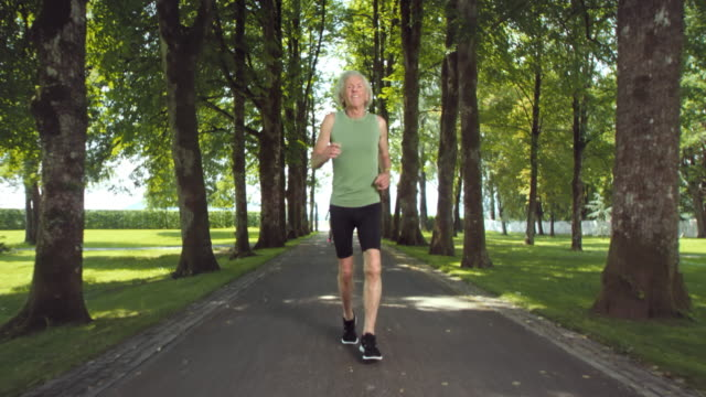 SLO MO TS Senior man jogging through tree avenue