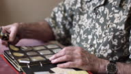 CU TU TD Senior man looking at album of old coins through magnifying glass / Bilbao, Vizcaya, Spain.