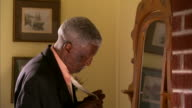 MS Senior man looking in mirror and adjusting tie / Halifax, Nova Scotia
