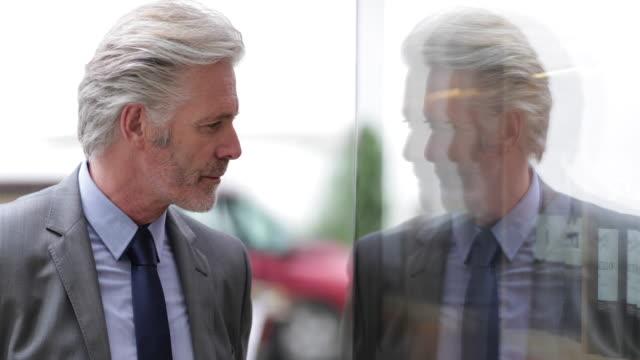 Senior man looking in store window