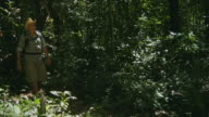 WS, Senior man looking through binoculars in forest, Manaus, Brazil