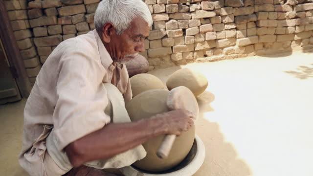 Senior man making earthen pot, Haryana, India