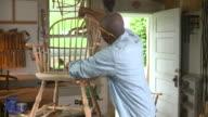 MS PAN Senior man making wooden armchair in workshop, Eastville, Virginia, USA