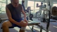 MS, senior man massaging bandaged knee, sitting in gym, USA, Pennsylvania, Solebury