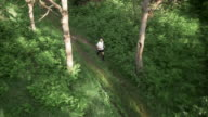 AERIAL Senior man on his run across a forest clearing