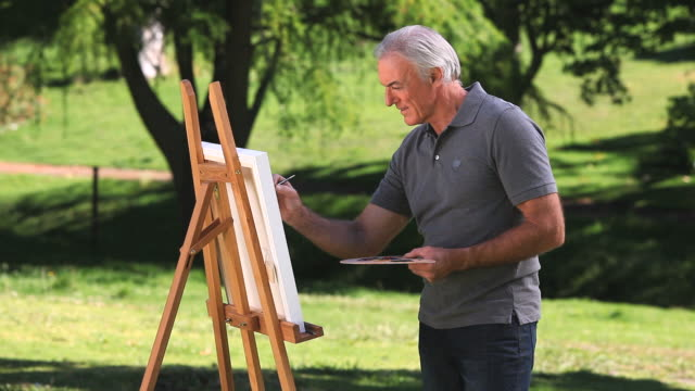 MS Senior man painting on canvas in Park / Cape Town, Western Cape, South Africa