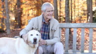 MS TU Senior Man Petting Yellow Labrador Retriever While Sitting on Park Bench / Richmond, Virginia, United States