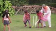 Senior man playing cricket with his grandchildren in holi festival