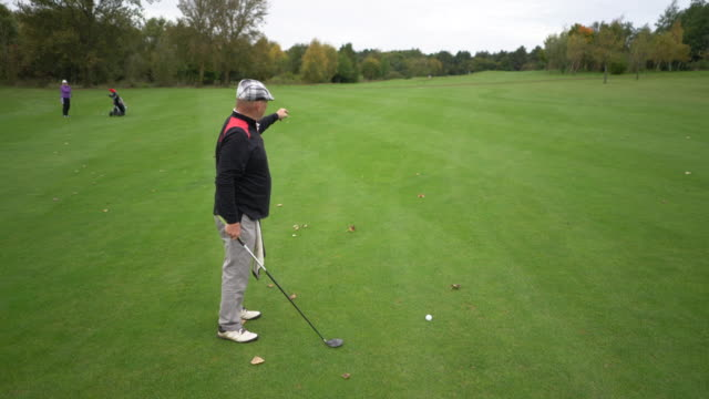 A senior man preparing to drive the ball from the fairway.