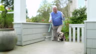 Senior man returning home with his dog from a walk