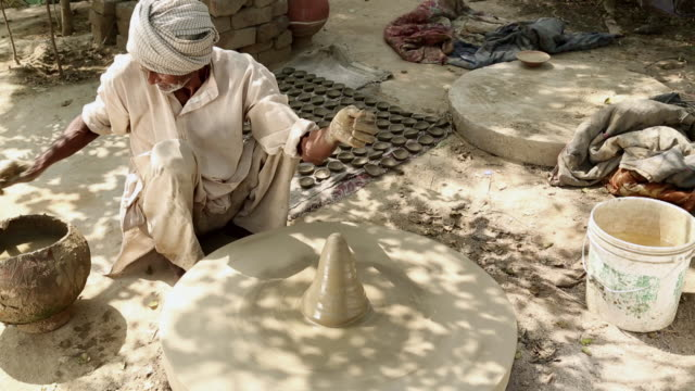 Senior man rotating clay pot, Haryana, India