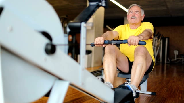 Senior man rowing at the gym