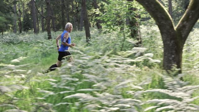 SLO MO DS Senior man running a forest trail marathon