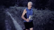 SLO MO DS Senior man running a trail marathon at sunset