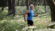 SLO MO DS Senior man running in the forest