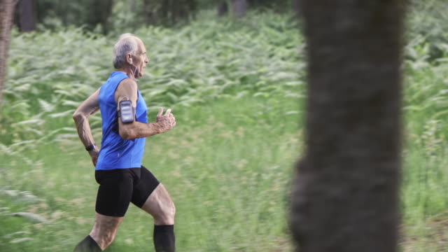 SLO MO DS Senior man running on forest trail