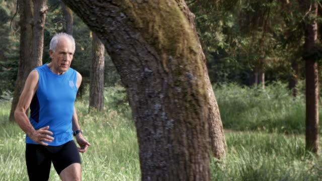 SLO MO DS Senior man running through forest in sunshine