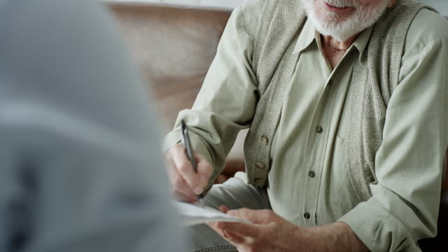 Senior man signing financial papers