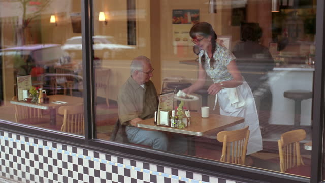 WS Senior man sitting in diner while waitress brings his check and removes empty plate / Seattle, Washington, USA