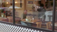 WS Senior man sitting in diner while waitress serves hamburger on plate, then man eats hamburger and drinks coffee / Seattle, Washington, USA