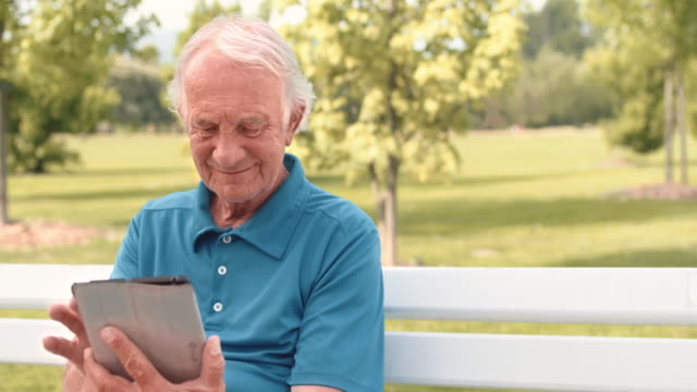Senior man sitting on the bench reading a newspaper on a tablet
