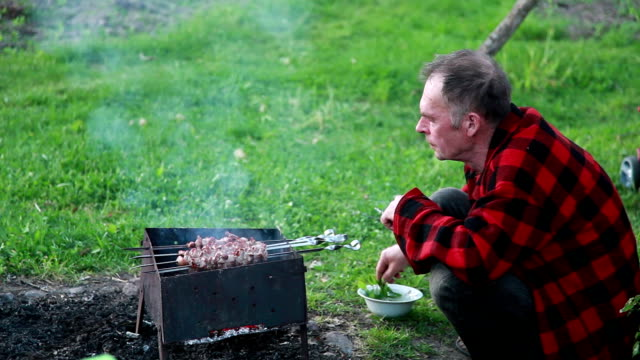 Senior man splashing the barbecue meat with water to avoid overcooking