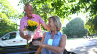 Senior man surprising his wife with flowers