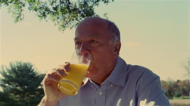 Senior man talking and drinking sip of orange juice
