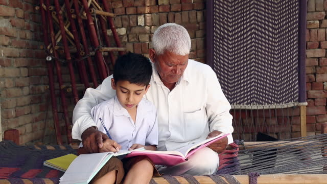 Senior man teaching to his grandson, Haryana, India