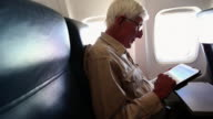 MS PAN Senior man using his tablet on airplane / Santa Fe, New Mexico, United States