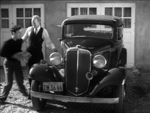 B/W 1938 senior man watching excited boy wiping car with cloth