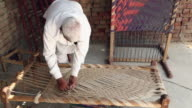 Senior man weaving cot, Haryana, India
