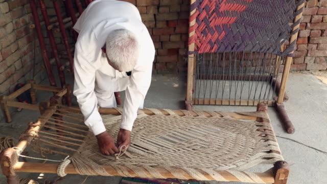 Senior man weaving cot, Haryana, India