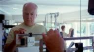 CU, senior man weighing himself on scale in gym, USA, Pennsylvania, Solebury