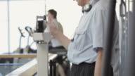 MS TU Senior man weighting scales on slide rule / Vancouver, British Columbia, Canada